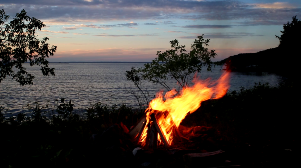 A bonfire on the beach of a large lake at sunrise, blue skies with an orange morning glow in the distance.