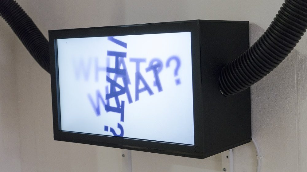 Image of a black rectangular lightbox with a white screen has the word what with a question mark written 3 times on it, black pipes leave the box on the left and right sides.
