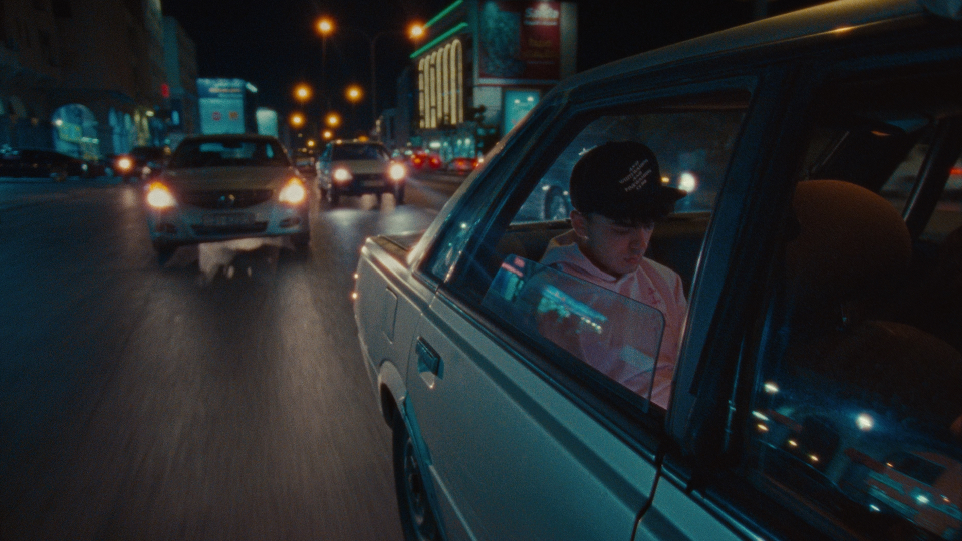 A young man sits in the back seat of a car with the window open, he wears a black cap and pink hooded sweatshirt. The car is driving down a busy street at night. Other cars follow behind with their lights on. Lit up buildings and streetlights overhead can be seen behind the car.