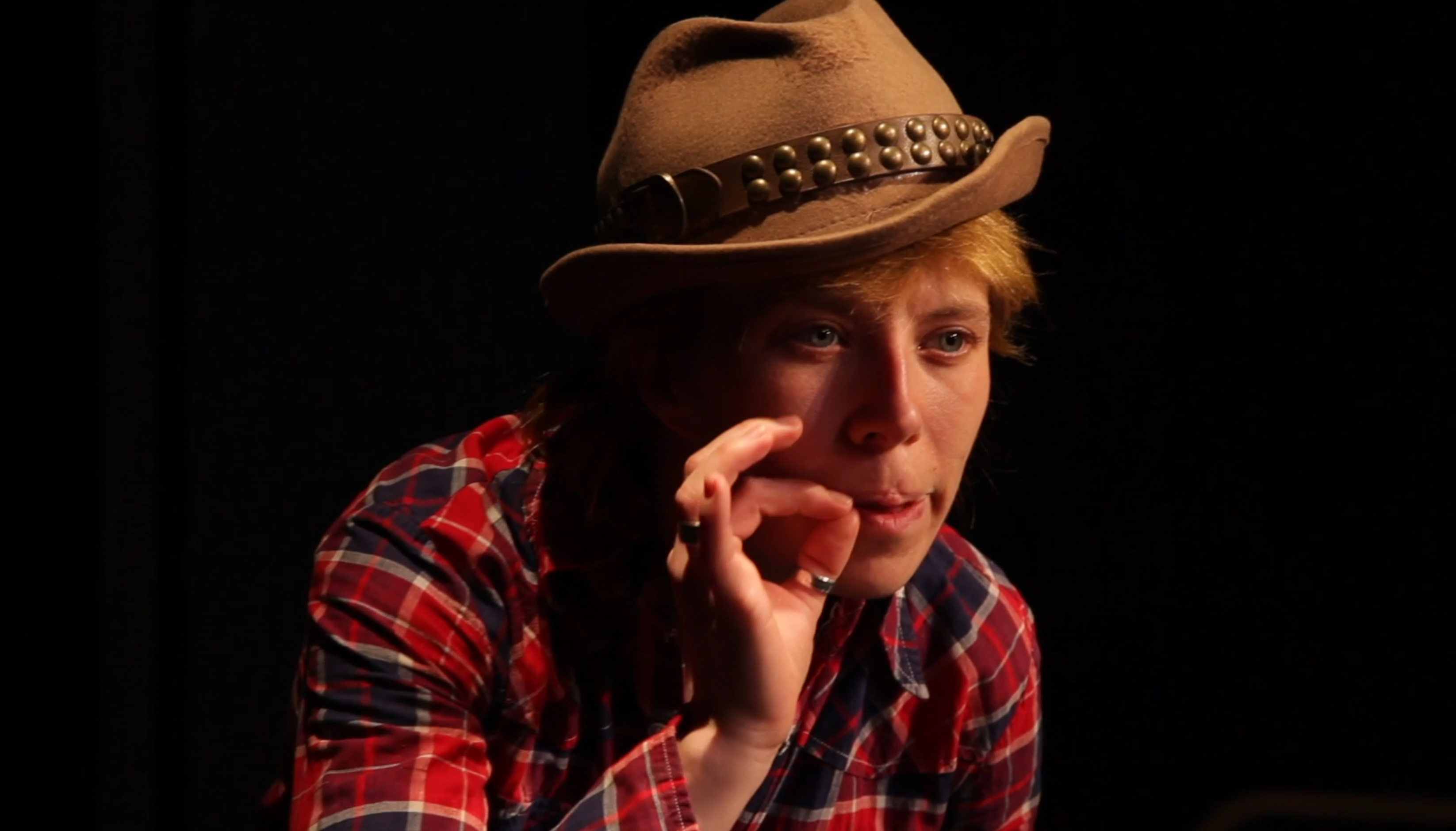 A person with cowboy hat and red and black plaid shirt imitates smoking a cigarette